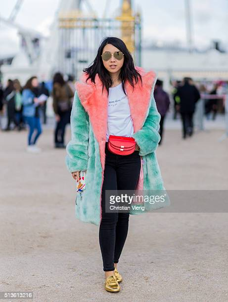 Yuwei Zhangzou wearing golden Gucci slippers a mint red fur coat black denim jeans and a red bag outside Carven during the Paris Fashion Week...