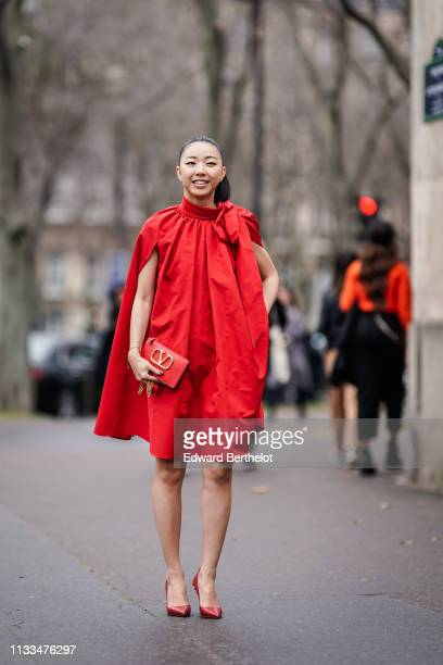 Yuwei Zhangzou wears a flowing pleated dress, a red Valentino bag, red heels studded shoes, outside Valentino, during Paris Fashion Week Womenswear...
