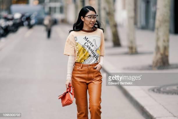 Yuwei Zhangzou wears a Merce Cunningham salmoncolored tshirt white sleeves an orange bag orange leather pants white shoes transparent sunglasses...
