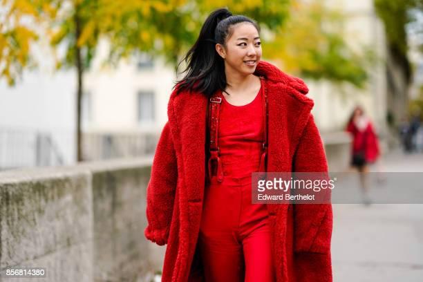 Yuwei Zhangzou wears a red fluffy coat a red top red pants silver shoes outside Shiatzy Chen during Paris Fashion Week Womenswear Spring/Summer 2018...