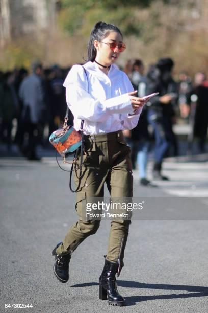 Yuwei Zhangzou wears a white shirt and green pants outside the Chloe show during Paris Fashion Week Womenswear Fall/Winter 2017/2018 on March 2 2017...
