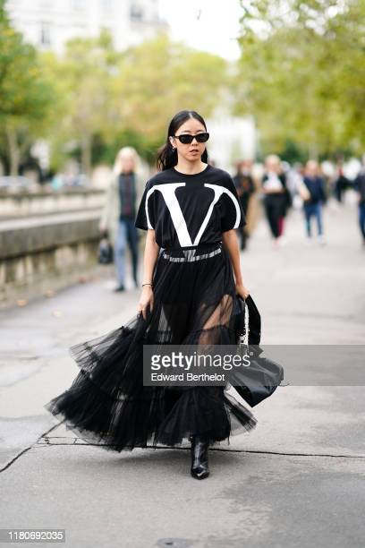 Yuwei Zhangzou wears sunglasses a black Valentino tshirt with printed large V logo a black lace mesh skirt a white studded bag from Valentino outside...