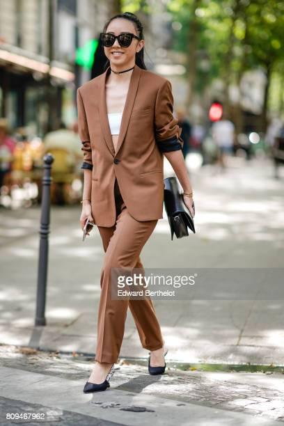 Yuwei Zhangzou wears sunglasses a brown blazer jacket brown suit pants and black shoes outside the Zuhair Murad show during Paris Fashion Week Haute...