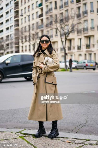 Yuwei Zhangzou wears sunglasses, a light brown trench coat, a white bag in the form of an elephant, black leather boots, outside Loewe, during Paris...