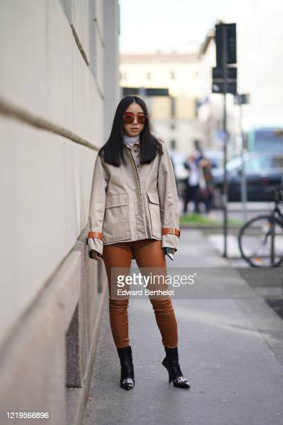 Yuwei Zhangzou wears sunglasses, a white turtleneck pullover, a gray jacket with long sleeves, brown leggings, Balenciaga black leather pointy boots,...