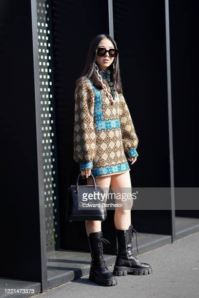 Yuwei Zhangzou wears sunglasses with a chain, a wool pullover / dress with printed geometric patterns, a black Gucci bag, black leather boots,...