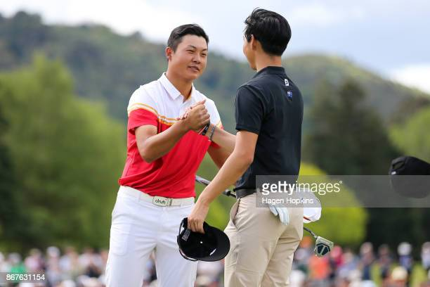 Yuxin Lin of China shakes hands with Min Woo Lee of Australia after winning the AsiaPacific Amateur Championship at Royal Wellington Golf Club on...