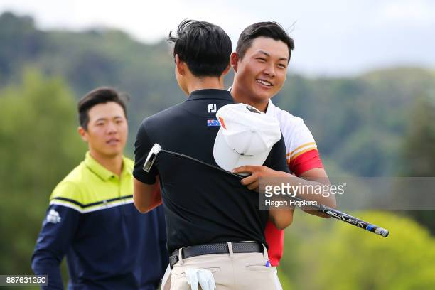 Yuxin Lin of China shakes hands with Min Woo Lee of Australia while Andy Zhang of China looks on after winning the AsiaPacific Amateur Championship...