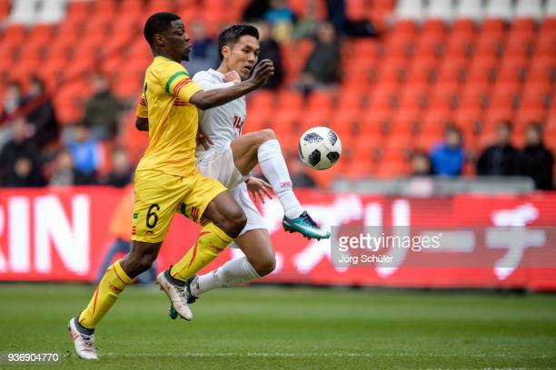 Yuya Kubo of Japan is challenged by Bakaye Dibassy of Mali during an international friendly between Japan and Mali at the Stade de Sclessin on March...