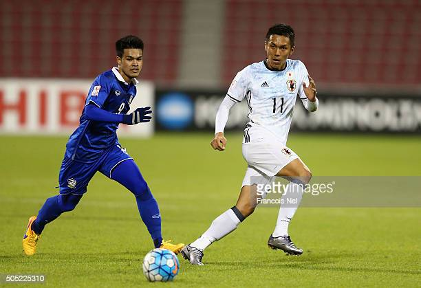 Yuya Kubo of Japan is closed down by Chayawat Srinawong of Thailand during the AFC U23 Championship Group B match between Thailand and Japan at Grand...