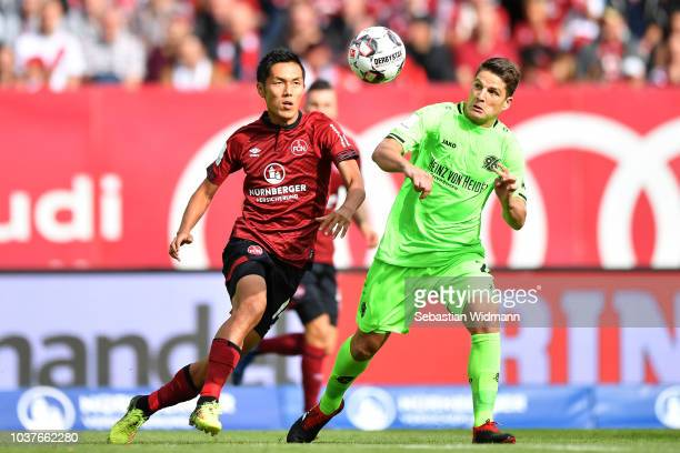 Yuya Kubo of Nuernberg and Pirmin Schwegler of Hannover compete for the ball during the Bundesliga match between 1 FC Nuernberg and Hannover 96 at...