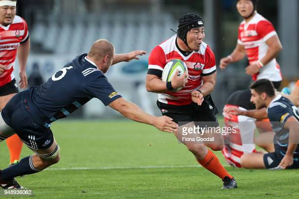 Yuya Odo of Japan A is tackled by Lyndon Dunshea of the Blues A during the curtain raiser match between Japan A and Blues A ahead of the round 10...