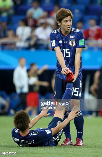 Yuya Osako helps Genki Haraguchi of Japan during the 2018 FIFA World Cup Russia Round of 16 match between Belgium and Japan at Rostov Arena on July 2...