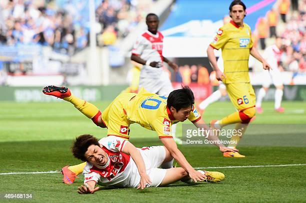 Yuya Osako of 1 FC Koeln is challenged by JinSu Kim of 1899 Hoffenheim during the Bundesliga match between 1 FC Koeln and 1899 Hoffenheim at...