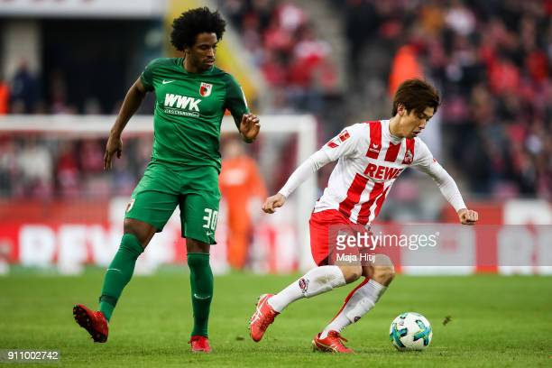 Yuya Osako of 1FC Koeln and Caiuby of Augsburg battle for the ball during the Bundesliga match between 1 FC Koeln and FC Augsburg at...