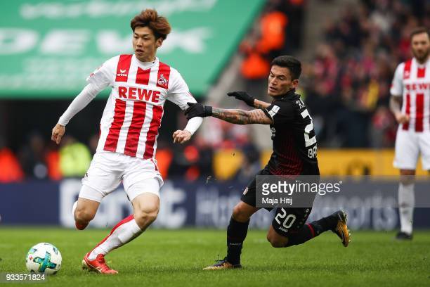 Yuya Osako of 1FC Koeln and Charles Aranguiz of Bayer Leverkusen battle for the ball during the Bundesliga match between 1 FC Koeln and Bayer 04...