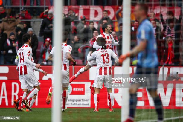 Yuya Osako of 1FC Koeln celebrates with Leonardo Bittencourt of 1FC Koeln and teammates after scoring his teams first goal during the Bundesliga...