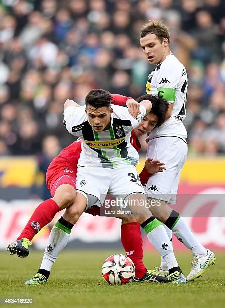 Yuya Osako of 1FC Koeln challenges Granit Xhaka of Borussia Moenchengladbach during the Bundesliga match between Borussia Moenchengladbach and 1 FC...