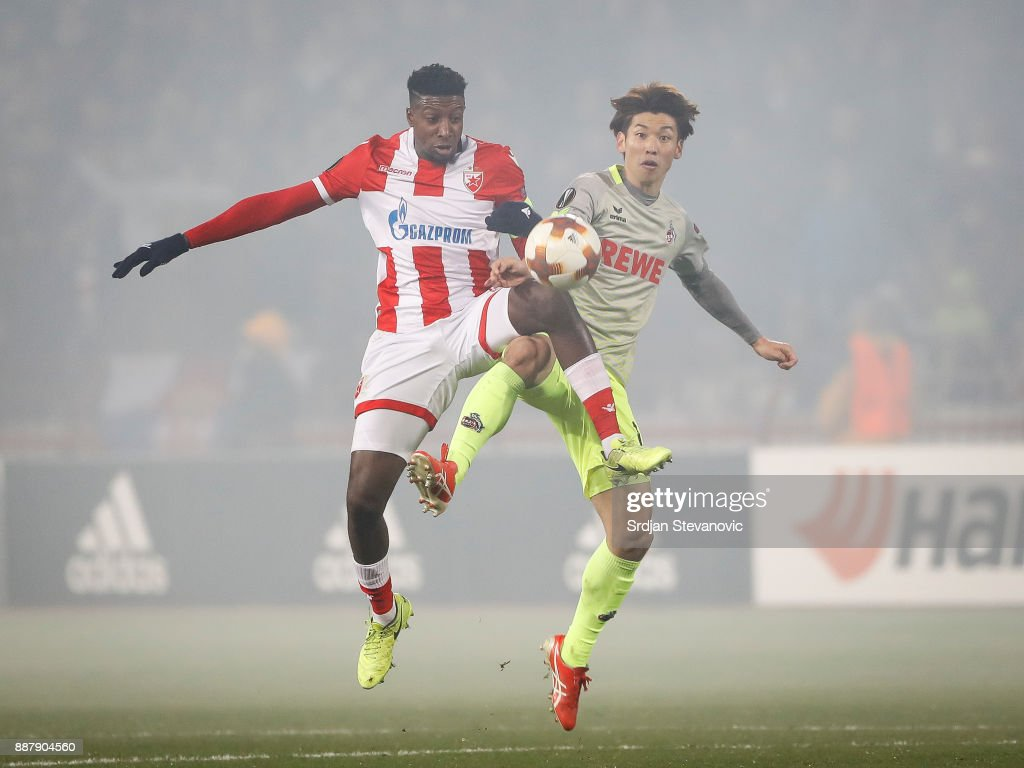 Yuya Osako (R) of FC Koeln competes for the ball against Mitchell Donald (L) of Crvena Zvezda during the UEFA Europa League group H match between Crvena Zvezda and 1. FC Koeln at stadium Rajko Mitic on December 7, 2017 in Belgrade, Serbia.