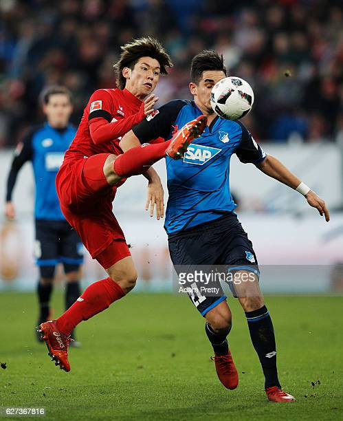 Yuya Osako of FC Koeln is challenged by Benjamin Huebner of TSG 1899 Hoffenheim during the Bundesliga match between TSG 1899 Hoffenheim and 1 FC...