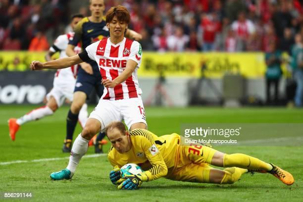 Yuya Osako of FC Koeln see a shot saved by Goalkeeper Peter Gulacsi of RB Leipzig during the Bundesliga match between 1 FC Koeln and RB Leipzig at...
