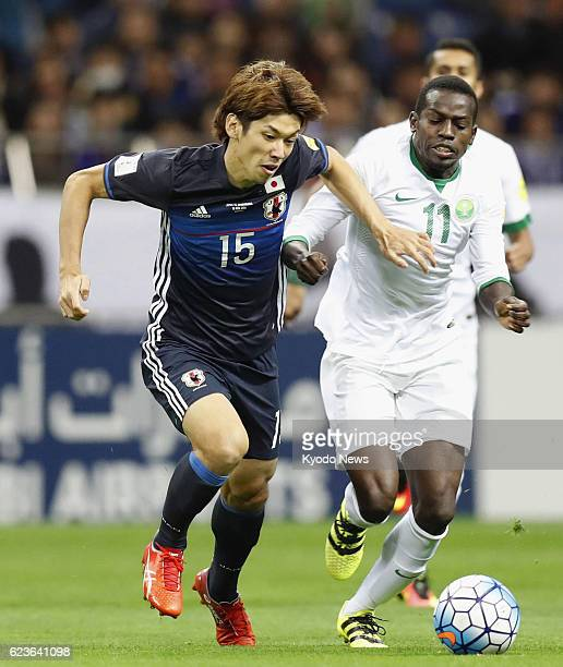 Yuya Osako of Japan and Abdulmalek Al Khaibri of Saudi Arabia battle for the ball during the first half of a Group B match of an Asian World Cup...