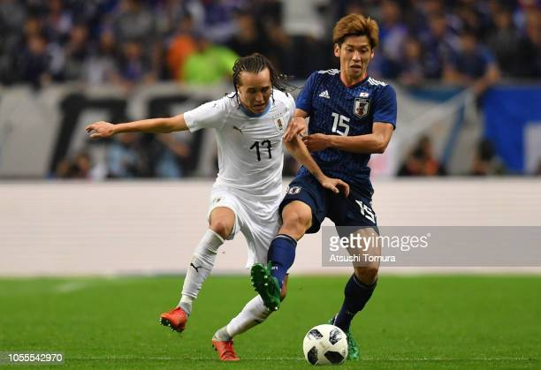 Yuya Osako of Japan and Diego Laxalt of Uruguay compete for the ball the international friendly match between Japan and Uruguay at Saitama Stadium on...