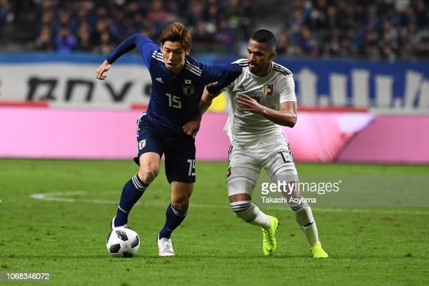 Yuya Osako of Japan and Yangel Herrera of Venezuela compete for the ball during the international friendly match between Japan and Venezuela at Oita...