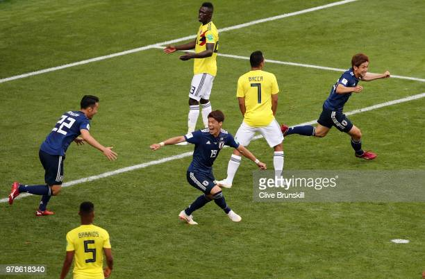 Yuya Osako of Japan celebrates with teammates after scoring his team's second goal as Davinson Sanchez of Colombia looks dejected during the 2018...