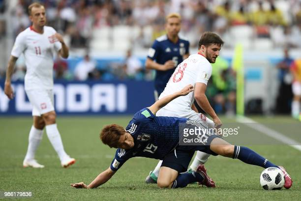 Yuya Osako of Japan challenge for the ball with Bartosz Bereszynski of Poland during the 2018 FIFA World Cup Russia group H match between Japan and...