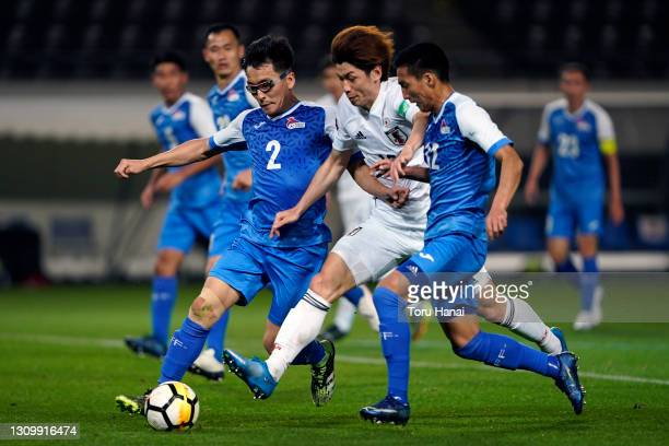 Yuya Osako of Japan competes for the ball against Tuguldur Galt and Oyunbaatar Otgonbayar of Mongolia during the FIFA World Cup Asian Qualifier...