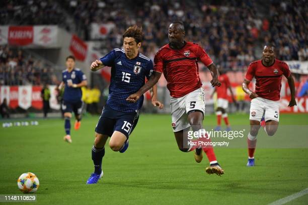 Yuya Osako of Japan dribbles the ball under the pressure from Daniel Cyrus of Trinidad and Tobago during the international friendly match between...