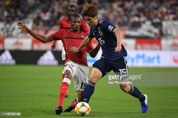 Yuya Osako of Japan dribbles the ball under the pressure from Kevan George of Trinidad and Tobago during the international friendly match between...