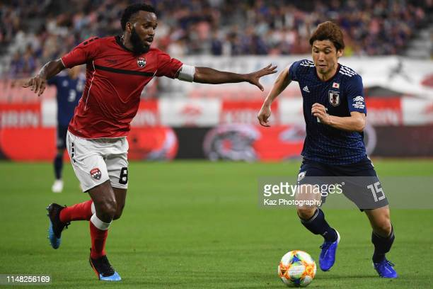 Yuya Osako of Japan dribbles the ball under the pressure from Khaleem Hyland of Trinidad and Tobago during the international friendly match between...