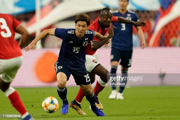 Yuya Osako of Japan in action against Daneil Cyrus of Trinidad and Tobago during the international friendly match between Japan and Trinidad and...