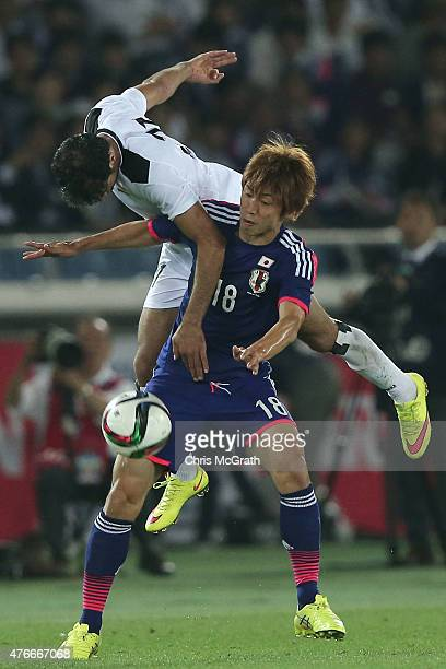 Yuya Osako of Japan is challenged by Saad Abdulameer of Iraq during the international friendly match between Japan and Iraq at Nissan Stadium on June...