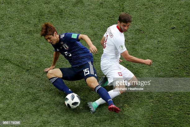 Yuya Osako of Japan is tackled by Bartosz Bereszynski of Poland during the 2018 FIFA World Cup Russia group H match between Japan and Poland at...