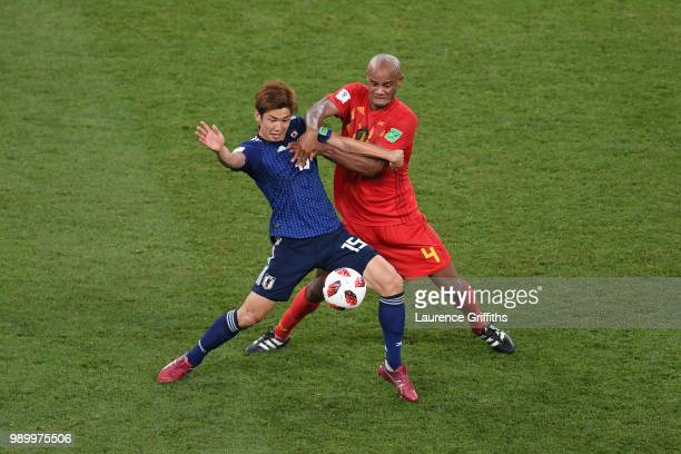 Yuya Osako of Japan is tackled by Vincent Kompany of Belgium during the 2018 FIFA World Cup Russia Round of 16 match between Belgium and Japan at...