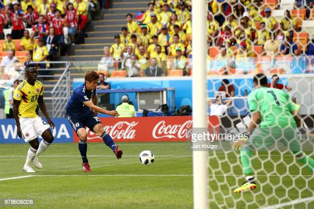 Yuya Osako of Japan shoots as Davinson Sanchez of Colombia looks on during the 2018 FIFA World Cup Russia group H match between Colombia and Japan at...
