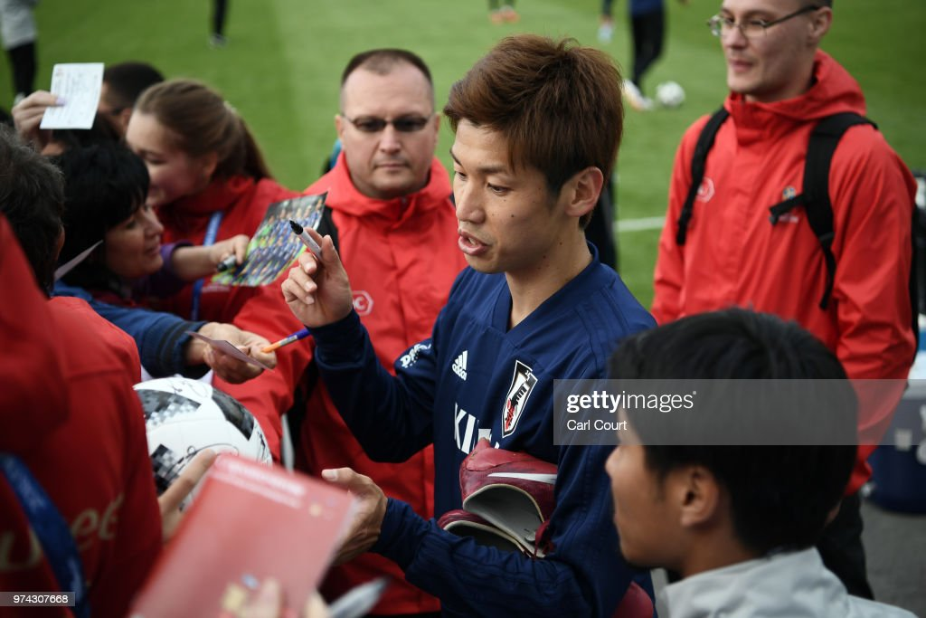 Yuya Osako of Japan signs autographs after a training session on June 14, 2018 in Kazan, Russia.