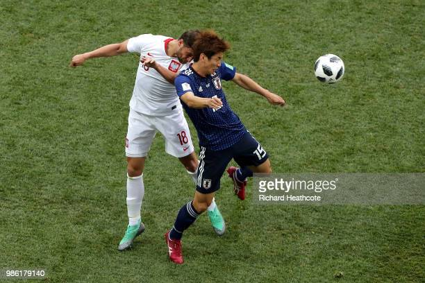 Yuya Osako of Japan wins a header over Bartosz Bereszynski of Poland during the 2018 FIFA World Cup Russia group H match between Japan and Poland at...