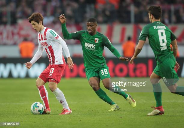 Yuya Osako of Koeln and Kevin Danso of Augsburg battle for the ball during the Bundesliga match between 1 FC Koeln and FC Augsburg at...