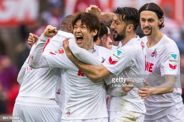Yuya Osako of Koeln celebrates his teams first goal with Dominic Maroh and Neven Subotic of Koeln during the Bundesliga match between 1 FC Koeln and...