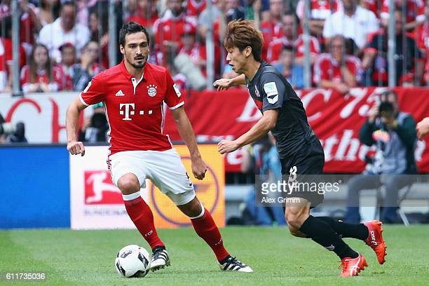 Yuya Osako of Koeln is challenged by Mats Hummels of Muenchen during the Bundesliga match between Bayern Muenchen and 1 FC Koeln at Allianz Arena on...