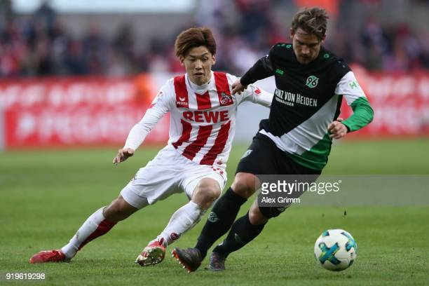 Yuya Osako of Koeln is challenged by Oliver Sorg of Hannover during the Bundesliga match between 1 FC Koeln and Hannover 96 at RheinEnergieStadion on...