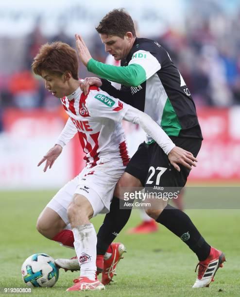 Yuya Osako of Koeln is challenged by Pirmin Schwegler of Hannover during the Bundesliga match between 1 FC Koeln and Hannover 96 at...