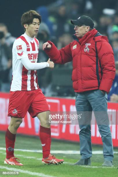 Yuya Osako of Koeln walks off after he received a red card and shakes hands with Peter Stoeger coach of Koeln during the Bundesliga match between FC...