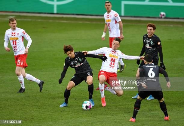 Yuya Osako of SV Werder Bremen battles for possession with Max Besuschkow of Jahn Regensburg during the DFB Cup quarter final match between Jahn...
