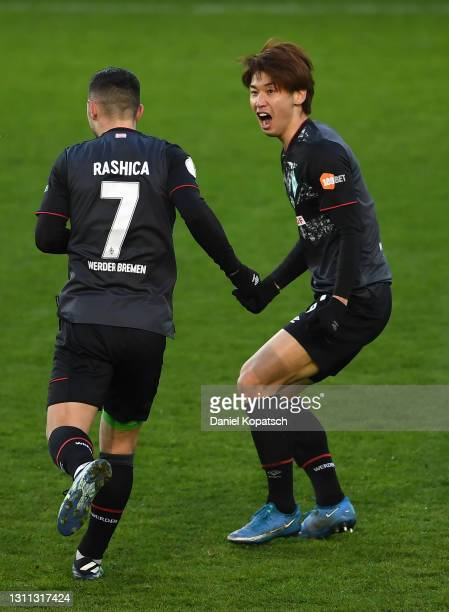 Yuya Osako of SV Werder Bremen celebrates with team mate Milot Rashica after scoring their side's first goal during the DFB Cup quarter final match...