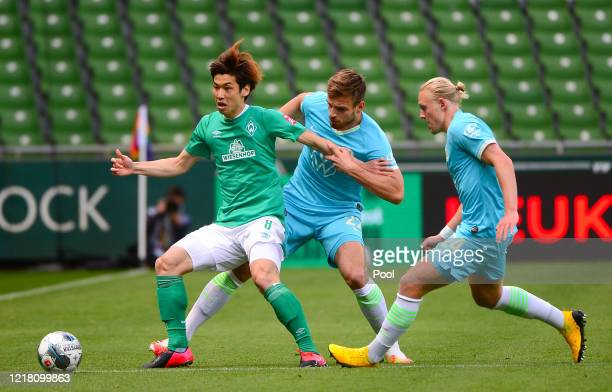 Yuya Osako of SV Werder Bremen is challenged by Marin Pongracic and Xaver Schlager of Wolfsburg during the Bundesliga match between SV Werder Bremen...